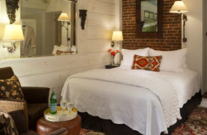 Queen bed with exposed brick wall at unique Bucks County PA hotel