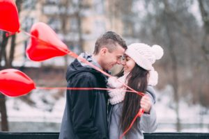 couple embracing with heart shaped ballons - give a gift certificate