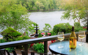 Wine and glasses on the riverside balcony of premium riverside room 8. Room with a view