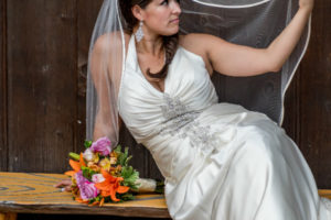 Rusitc bride sitting on bench examining veil