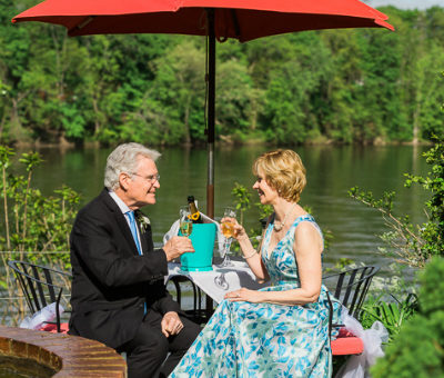 Elopement in Bucks County, PA - wedding couple riverside champagne toast under red umbrella