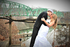 Elope in PA, newlyweds kissing by the river at Bridgeton House