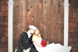 Rustic wedding backdrop for wedding couple sitting on rustic bench