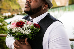 Groom holding bouquet by river