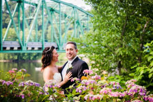 Bride and Groom in Garden with River Backdrop